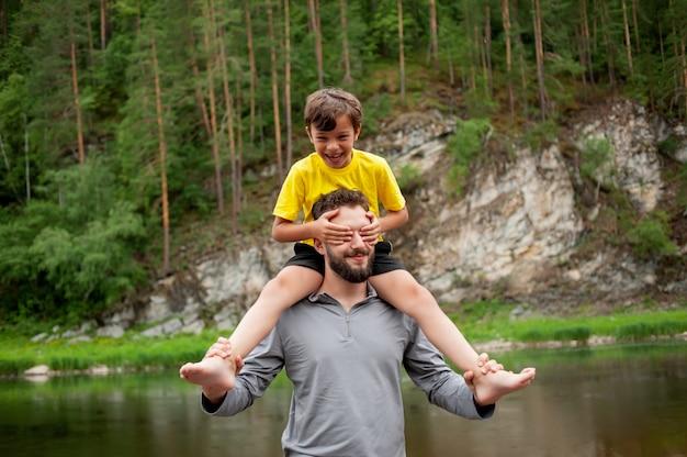 Отец и сын улыбаются, проводя время вместе. маленький мальчик сидит на шее отца
