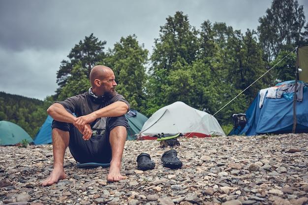 Турист бородатый человек отдыхает на реке. остановитесь и отдохните, путешествуя на природе.