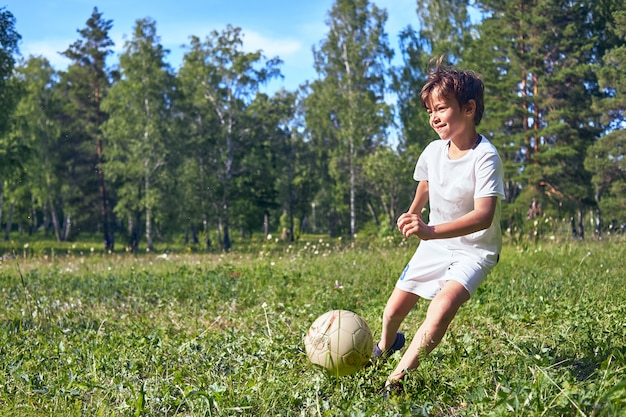 Малыш пинает футбольный мяч на поле