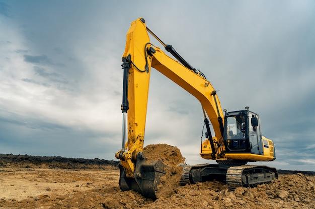 採石場の建設現場にある黄色の大型建設掘削機。産業イメージ
