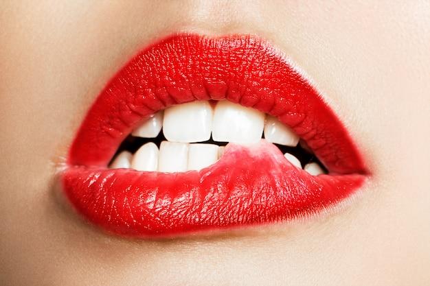 唇を噛む女性の白い歯のクローズアップ