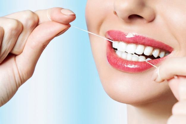 若い美しい女性は歯のクリーニングに従事しています