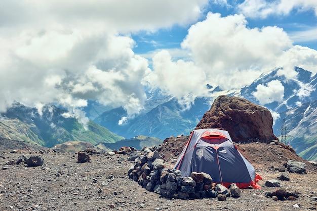 山のテントクライマー。山頂を背景に。アルピニストキャンプ