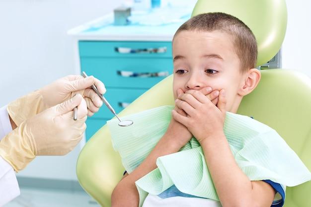 歯科用椅子で怖い子供の肖像画。少年は歯医者に診てもらうのを恐れて、手で口を覆っています。子供の歯科。