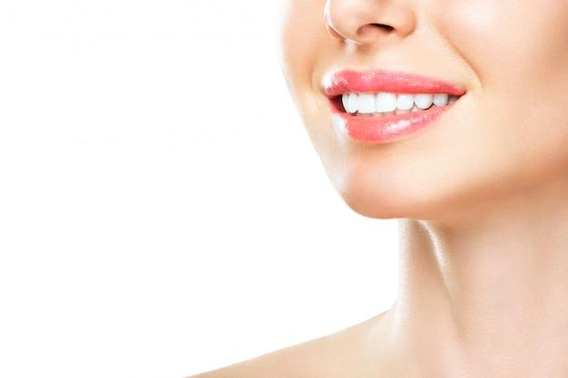 若い女性の完璧な健康な歯の笑顔。歯のホワイトニング。歯科医院の患者。画像は口腔ケア歯科、口腔病学を象徴しています。白い背景を分離します。
