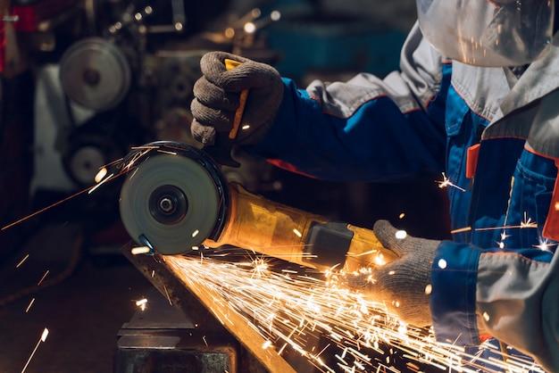 Слесарь в спецодежде и защитных очках работает на производстве
