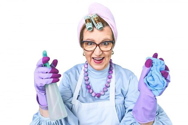 青の背景に分離されたダストクリーニングブラシでエプロンで幸せな古いクリーニング女性の肖像画。クリーニングのための特別なユニフォームおよび専門機器