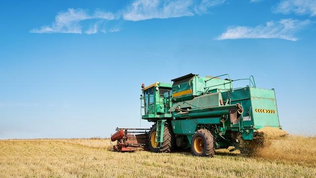 コンバインハーベスターは熟した小麦を収穫します。農業イメージ