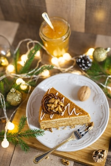 レーズンとナッツの木製テーブルの上のサワークリームと自家製蜂蜜ケーキ