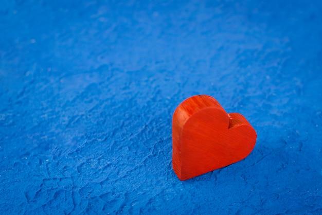 青いテクスチャ背景に赤い木の心。テキスト用のスペースと愛とロマンスの概念。デスクトップ用のバレンタインの壁紙用に開きます。