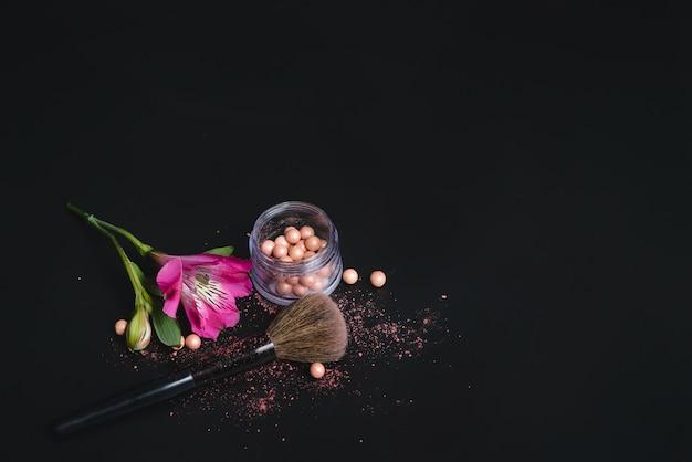 黒の背景に真珠の赤面、花、化粧ブラシ