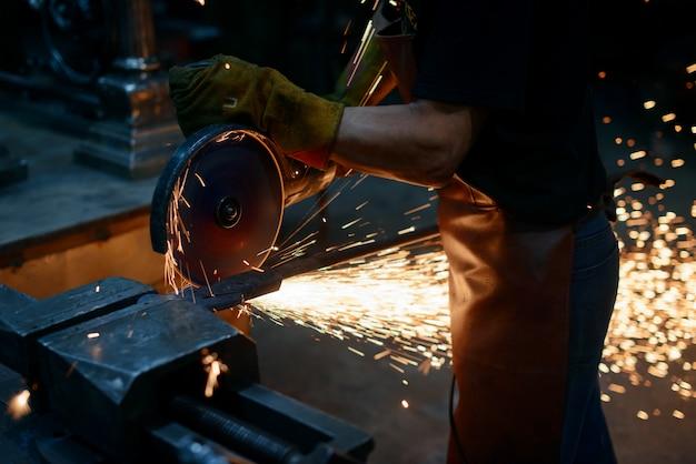 Работа на металле. мастер режет металл. шлифовка поверхности дисковой пилой. искры летят из-за сильного трения. работа в гараже