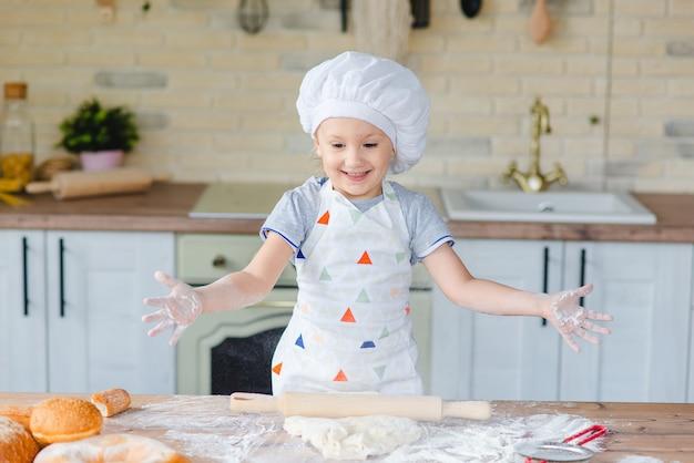 Милая девочка в костюме шеф-повара готовит на кухне