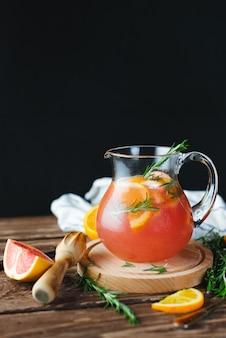 古い木製のテーブルにグレープフルーツとローズマリーの新鮮な夏のレモネード。夏のコンセプト。