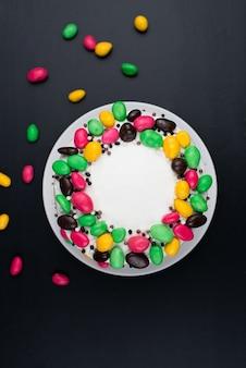 黒い表面にクリームとキャンディーの装飾が施された誕生日ケーキ