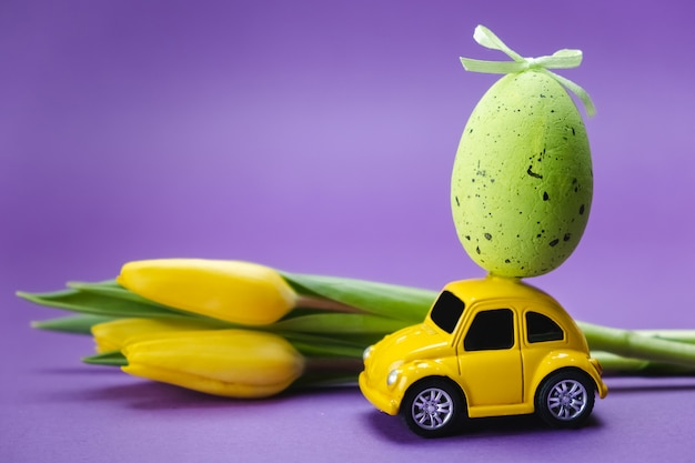 Желтый игрушечный автомобиль несет зеленое яйцо на фиолетовой поверхности