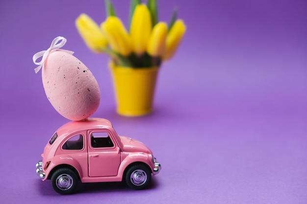 Розовая игрушечная машинка несет розовое яйцо на фиолетовой поверхности