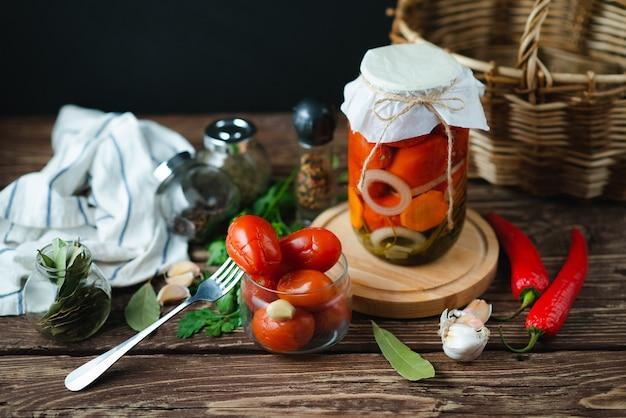 ピクルストマトの自家製瓶。漬物および缶詰製品。菜食主義の概念
