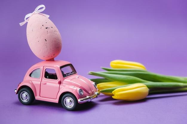 Розовая игрушка ретро автомобиль с яйцом на крыше и желтыми тюльпанами на фиолетовой поверхности