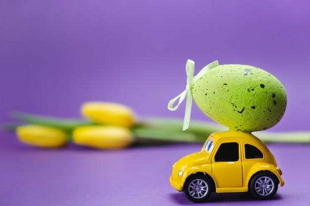 Желтый ретро игрушечный автомобиль доставляет яйцо на крышу и желтые тюльпаны на фиолетовую поверхность