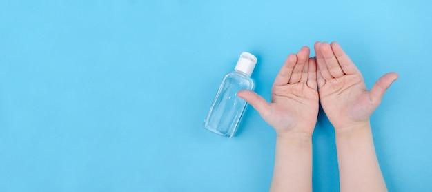 手洗い用ジェル。子供の手に消毒ハンドジェルを注ぐ。バナーパノラマ