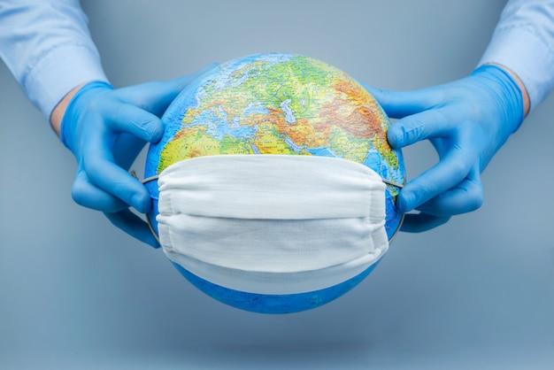 医療用手袋をはめた手が地球に防護マスクをかけます。世界コロナウイルス/コロナウイルス攻撃の概念。ウイルスとの戦いの概念。