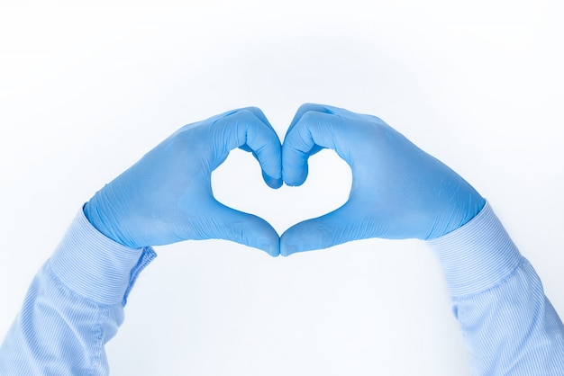 白い背景に医療用手袋で思いやりのある医者の手が指で心を示し、専門家が私たちの健康を世話します:医療の概念、テキストのための場所