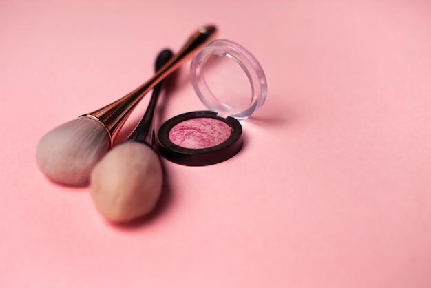 Макияж кисти и румяна на розовом фоне. концепция красоты. крупный план с пространством для текста