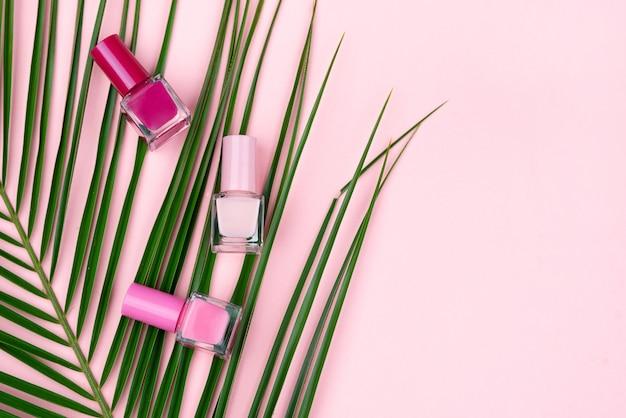Лаки для ногтей и пальмовая ветвь на розовом фоне