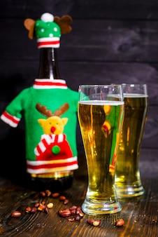 Пиво в бокалах и бутылка с новогодним украшением