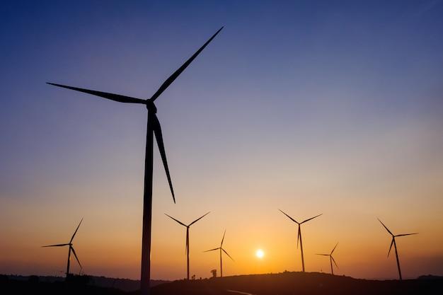 夕焼け空と電気のシルエット風力タービンフィールドを生成します