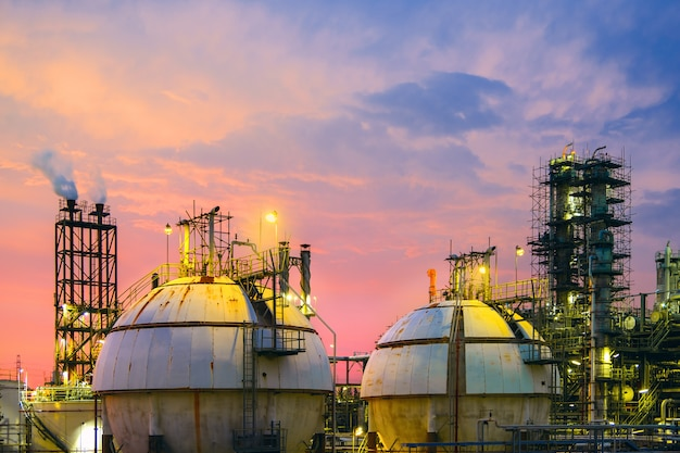 ガス貯蔵球タンク、夕焼け空の背景に石油化学プラント、石油産業の製造、ガスおよび石油精製産業プラントの機器を閉じる