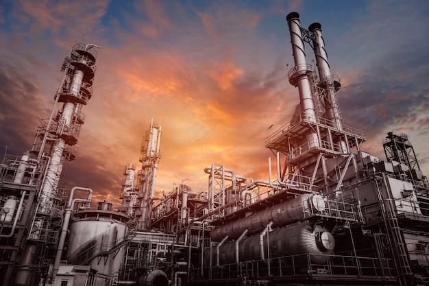 空の夕焼けに工場で炭化水素を分解する工業炉と熱交換器、石油化学プラントの機器のクローズアップ