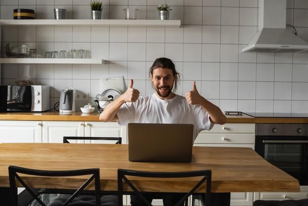 Взволнованный бизнесмен, радуясь успешному проекту. счастливый человек держа большие пальцы руки вверх в воздухе и смотря компьтер-книжку пока сидящ на кухне дома.