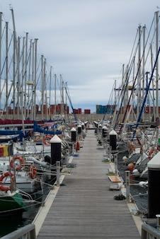 豪華なヨットや地中海のバレンシアポートのボート。水の反射。春の初め、白いヨットがスペインのバレンシア港に停泊します。曇り空。