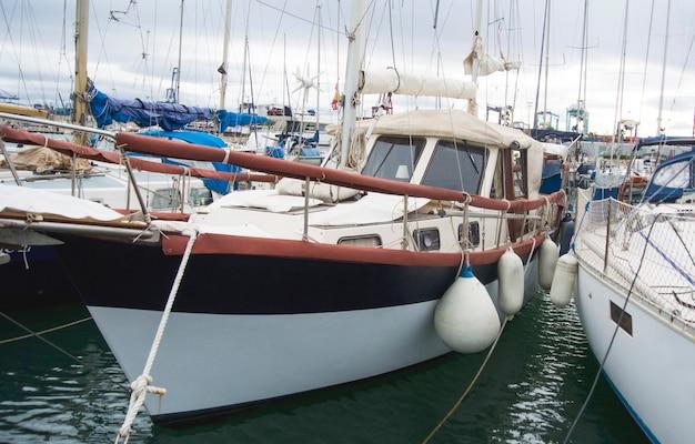 地中海のバレンシア港のボート。水の反射。春の初め、白いヨットがスペインのバレンシア港に停泊します。曇り空。
