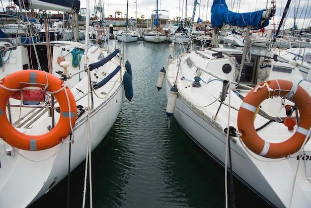 地中海のバレンシア港の白いボート。水の反射。春の初め、白いヨットがスペインのバレンシア港に停泊します。曇り空。