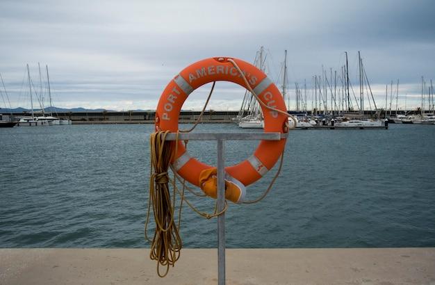ヨットのマリーナで救命浮輪。ボートドックの赤い丸。豪華なヨットや地中海のバレンシアポートのボート。白いヨットはバレンシアのスペインの港にあります
