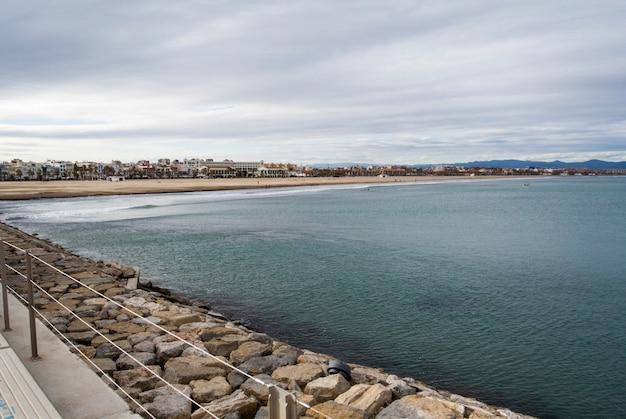 海の波と曇りのビーチのパノラマ。スペイン、バレンシアの地中海の空の春のビーチ。