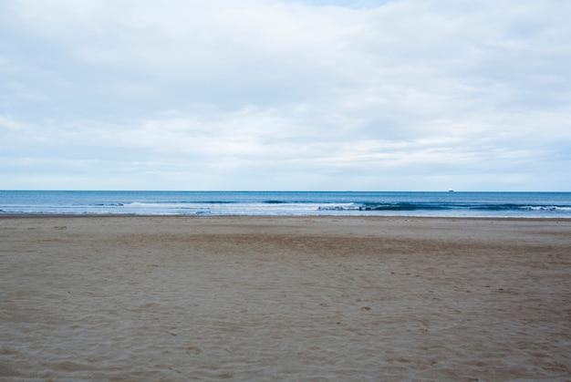 海の波と曇りのビーチ。スペイン、バレンシアの地中海の空の春のビーチ。