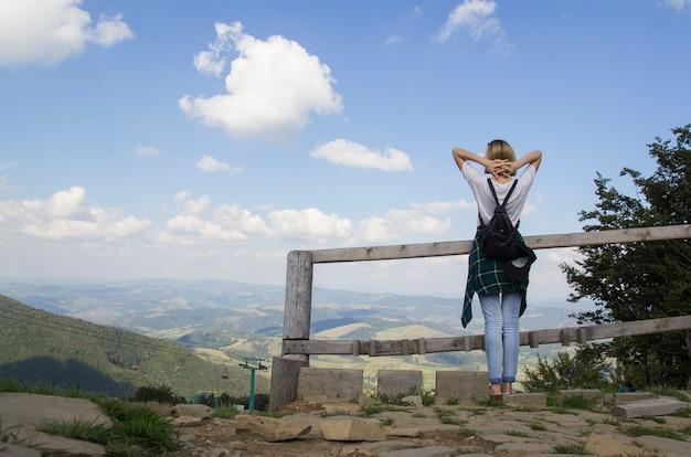 上から夕日を眺めながらハイキング旅行の女の子。山を背景にリラックスしてリフレッシュする女の子は、高山、白い青い雲の風景です。空を見て山の上の少女
