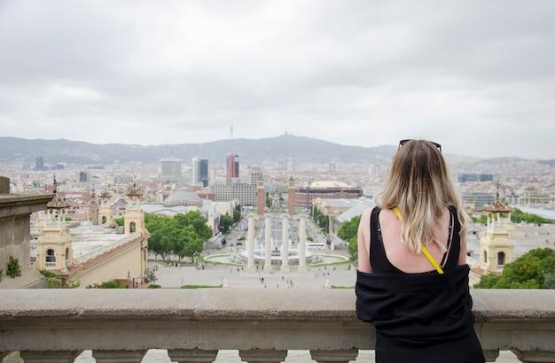 カタルーニャ国立博物館とバルセロナの噴水のカスケードからのバルセロナ市のパノラマを長い髪の黒いシャツに戻った美しい少女。カタルーニャ、スペイン。