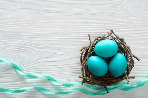 Концепция пасхи с голубыми яичками в гнезде на деревянном столе.