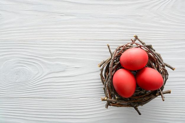 木製のテーブルに巣に赤い卵をイースターコンセプト。