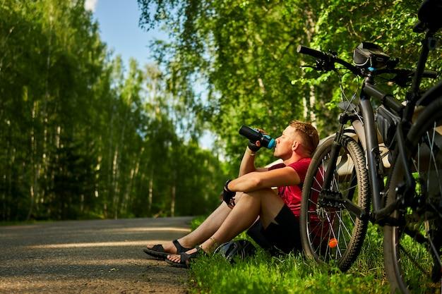 疲れた男性サイクリストは道路の脇に座って、ボトルから水を飲みます。
