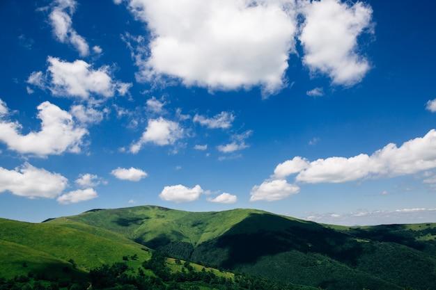 緑の山々の上の白い雲。壁紙の夏の山の風景