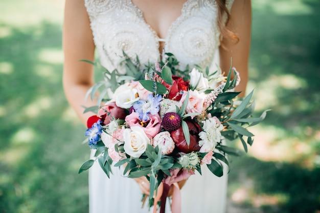 Свадебный букет цветов, проведенных крупным планом невесты. зеленый фон