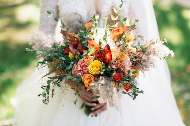 Невеста держит большой свадебный букет. букет осенних цветов