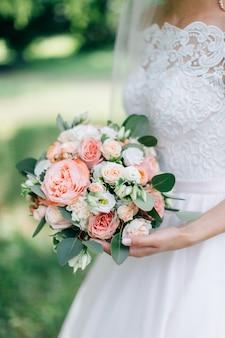 Невеста в белом платье, холдинг красивый букет. зеленый фон