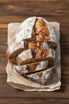 スライスした焼きたてのパンのクローズアップ。ベーキングペーパーのそばパン。木製の表面と背景